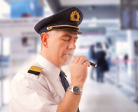 Airline pilot with e-cigarette Royalty Free Stock Photo