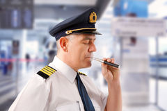 Airline pilot with e-cigarette Stock Image