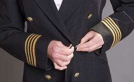 Airline pilot fastening uniform jacket Stock Image