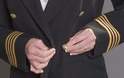 Airline pilot fastening uniform jacket Royalty Free Stock Photos