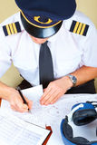 Airline pilot filling in papers. Airline pilot wearing hat, shirt with epaulets and tie filling in and checking papers flight plan, log book and weather forecast royalty free stock photography