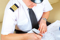 Airline pilot filling in papers in ARO Royalty Free Stock Photos