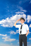 Airline pilot looking upwards. Cheerful airline pilot wearing uniform with epaulets and hat looking upwards, standing over a beautiful blue cloudy sky with royalty free stock image