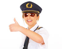 Airline pilot thumb up. Beautiful woman airline pilot wearing uniform with epaulets showing thumb up gesture of approval, standing isolated on white background royalty free stock images
