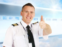 Airline pilot thumb up. Cheerful airline pilot wearing uniform with epauletes showing thumb up gesture of approval, standing over modern background royalty free stock images
