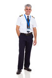 Airline pilot uniform. Cheerful middle aged man wearing airline pilot uniform on white background Stock Image