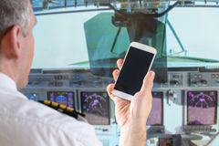 Airline pilot using smart phone Stock Image