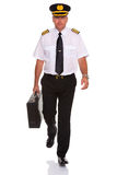 Airline pilot walking carrying flight case. Royalty Free Stock Image
