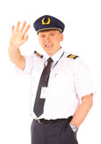 Airline pilot waving. Cheerful airline pilot wearing uniform with epaulets and hat waving, standing isolated on white background royalty free stock images