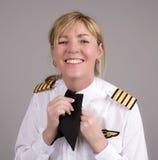 Airline pilot wearing a uniform cravat. Senior female airline captain clipping her uniform cravat Stock Photo