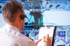 Airline pilot. Wearing uniform with epauletes and headset, writting on notepad inside airliner stock photography