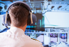 Airline pilot. Wearing uniform with epaulettes and headset working in airliner during flight royalty free stock photos