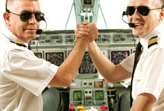 Airline pilots. Two airline pilot wearing uniform with epaulettes and headset working in airliner during flight royalty free stock images