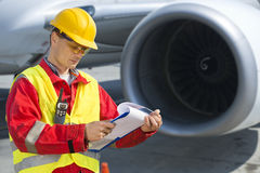 Airline safety. Engineer going through a pre-flight checklist royalty free stock image
