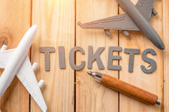 Airline tickets word and toy airplane. On wooden background Royalty Free Stock Photo