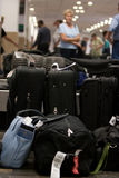 Airline travel. Baggage sits beside the conveyor belt in an international airport as travellers wait to claim them Royalty Free Stock Images