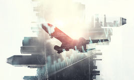 Airliner above business center. Double exposure of airplane and moden cityscape stock image