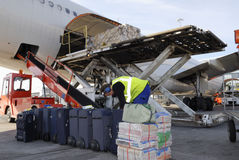 Airliner being loaded with luggage. Airplane, airliner being loaded with luggage and cargo, airport activities Stock Photo