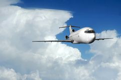 Airliner coming out of clouds. Trijet coming out of clouds at high altitude Stock Photography