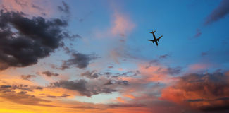 An Airliner Cruises Through a Sunset Sky Stock Image