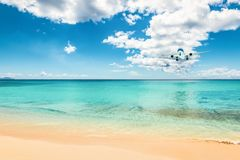Airliner in the distance above the beautiful Caribbean ocean, will land at the beach of Sint Maarten. Airplane landing above tropical Maho beach in Sint Maarten royalty free stock photography
