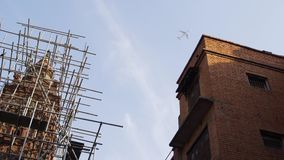 Airliner flies over a construction scaffold and residential houses. The passenger airliner flies over a well of the yard in which there is recovery work with stock footage