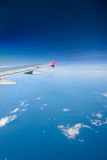 Airliner flying over clouds Stock Images