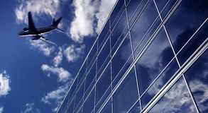 Airliner flying over high office buildings Royalty Free Stock Images