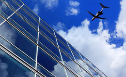 Airliner flying over office buildings Royalty Free Stock Photography