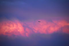 Airliner flying in the sky with red clouds Stock Photos