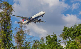 Airliner Landing Low Near Trees Royalty Free Stock Images