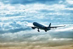 Airliner Landing On Evening Sky Stock Photos