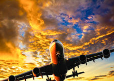 Airliner landing under dramatic skies. Composite image of airplane landing under dramatic stormy sky at sunset. Composite Image Stock Photography
