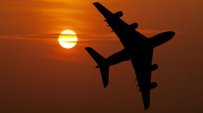 Airliner over red sunset Royalty Free Stock Images