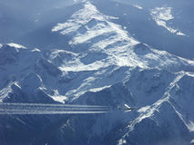 Airliner over snow covered mountains Royalty Free Stock Image