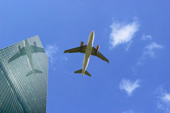 Airliner with Reflection. An Airliner in Flight with Reflection in Skyscraper Glass Stock Photo