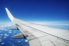 Airliner wing in flight on sky background. Airliner wing in flight on blue sky background Royalty Free Stock Photo