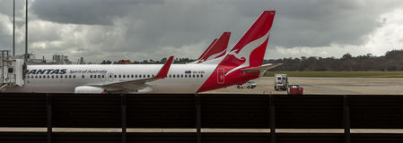 Airliners Taking Passengers. MELBOURNE/AUSTRALIA - SEPTEMBER 22, 2015: Heavy Jetliners parked at passenger terminal taking on passengers Royalty Free Stock Photo