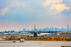 Airlines and Ground Services. Airports runway and ground services waiting to service. With an airplane in-front of city Royalty Free Stock Photo