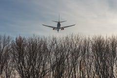 Airlplane grande del pasajero que vuela bajo sobre árboles forestales contra el cielo azul claro durante puesta del sol El aterri imagen de archivo