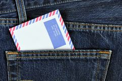 Airmail Envelope. An airmail envelope in the back pocket of denim trousers Royalty Free Stock Photo