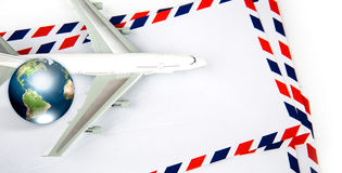 Airmail envelope with model airplane and earth. (Elements of this image furnished by NASA Stock Photo