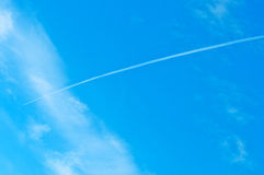Airoplane on a cloudy blue sky Stock Photography