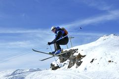 Airoski: skier performing a long jump. Airoski: a skier crouching in a long jump Royalty Free Stock Images