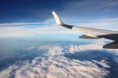 Airplain over clouds. Aerial view on white clouds from airplane (wing view Stock Image