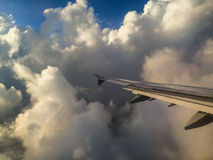 Airplain Wing in the sky. Picturesque cloudscape view from the plane window Royalty Free Stock Photo
