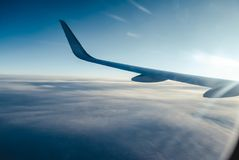 Airplain wing view thrue porthole. In the sky Stock Photos