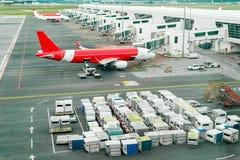 Airplains och fraktbehållare i flygplats Arkivfoton