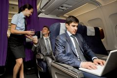 In airplane. Image of busy male typing on laptop with pretty stewardess giving glass of water to successful businessman on background