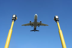 Airplane. A landing airplane framed between two airport guide light poles Stock Photos